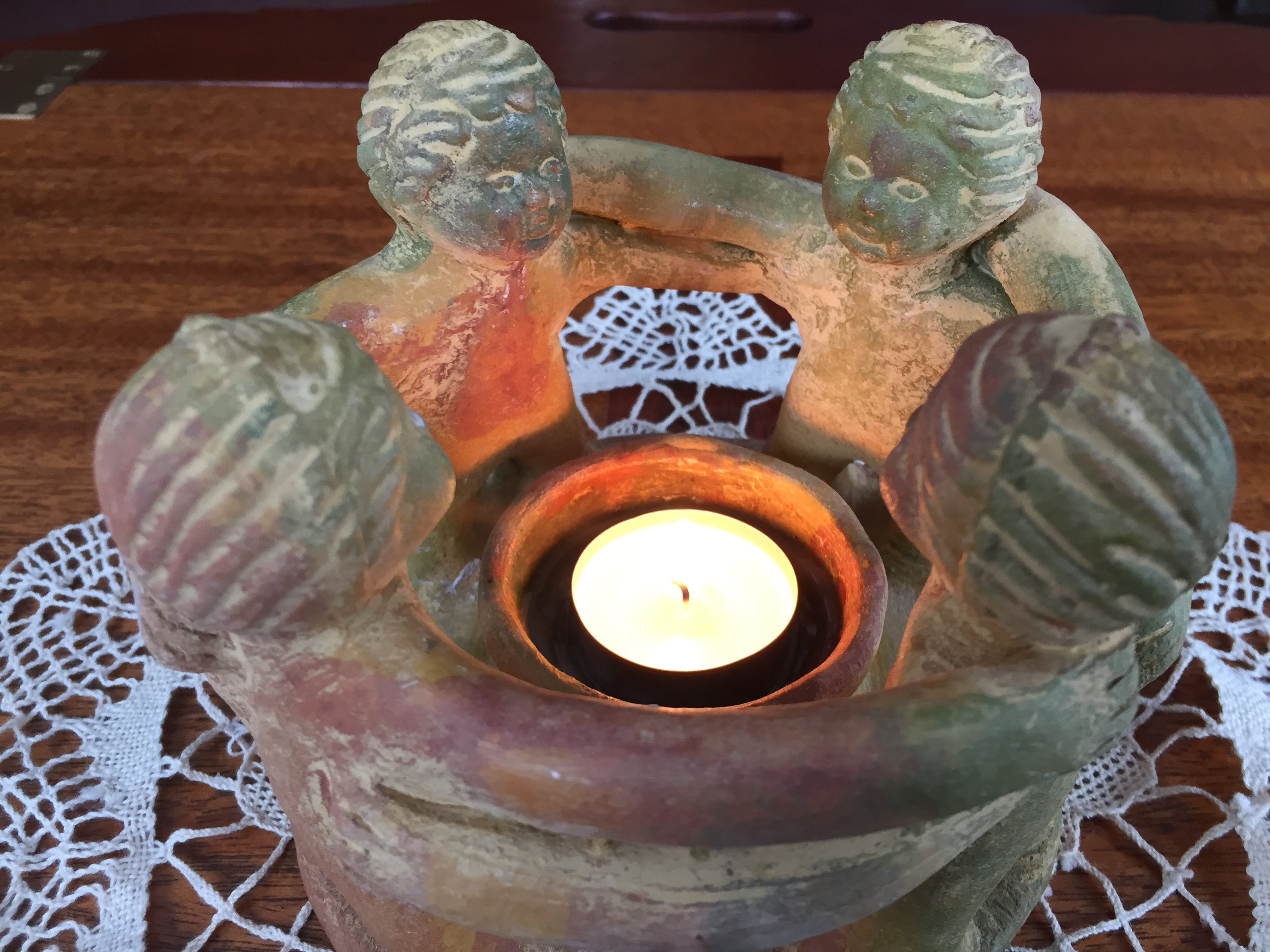candle holder circled by carved figures
